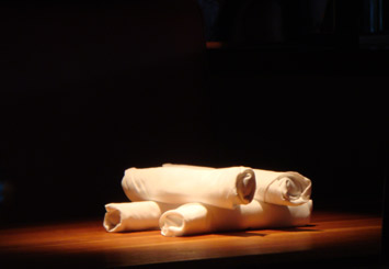 Photograph of dinner napkins rolled up and stacked on a dining table